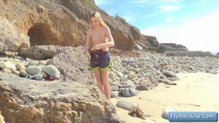 वह समुद्र तट के किनारे पर बैठती है और अपने स्तन और नग्न गांड दिखाती है